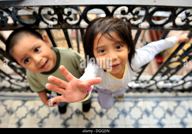 Two indigenous girls, one reaches up, living with their community in a dilapidated house from the colonial period - Stock Image
