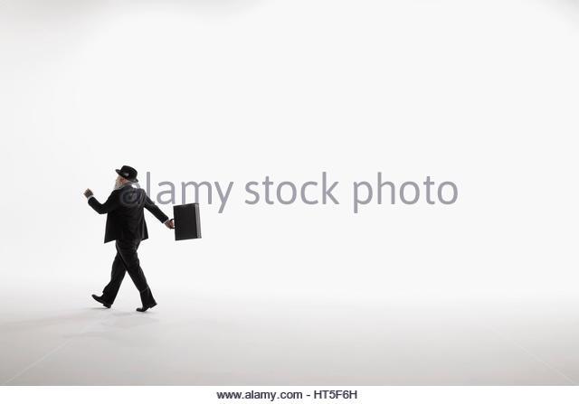 Businessman walking, swinging briefcase against white background - Stock-Bilder