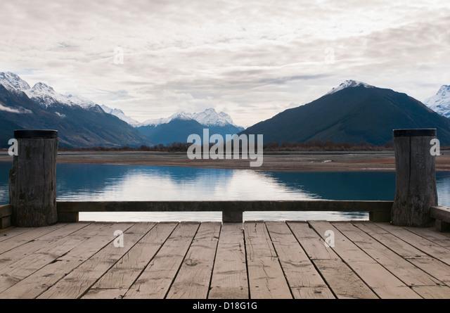 Wooden dock on still rural lake - Stock Image