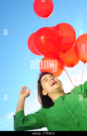 Asian American teenager girl happy holding red balloons - Stock Image