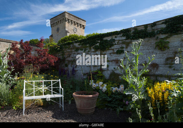 A corner of the Velvet Border with a stylish bench and within Easton Walled Garden, Lincolnshire, England - Stock Image