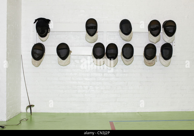 Fencing masks hanging from wall - Stock Image