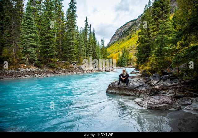 Caucasian woman sitting on rock near mountain river - Stock Image