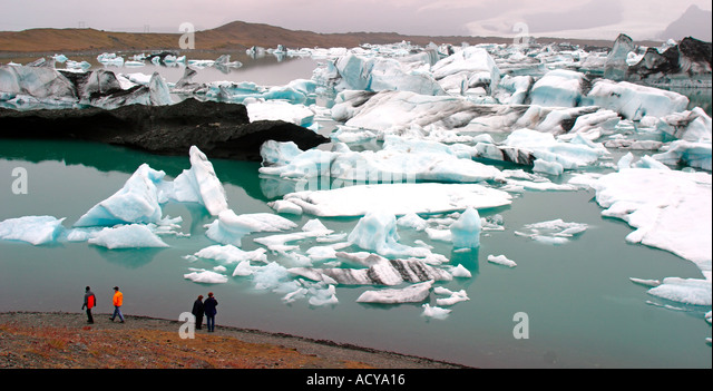 Iceland Jokulsarlon Glacial Lagoon Icebergs melting sunset near vulcano Jatnajoekull tourists watching - Stock Image