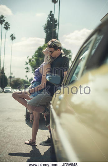 Young romantic couple, leaning against car - Stock-Bilder
