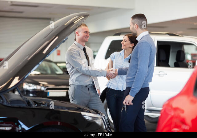 Man shaking hand of a car dealer in front of a car - Stock Image