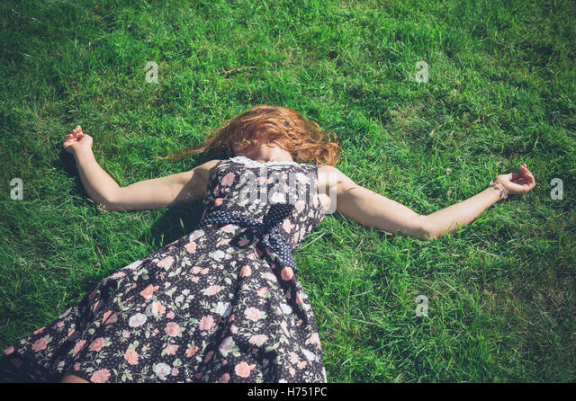 A young woman wearing a dress is lying in the green grass on a sunny summer day - Stock Image