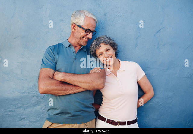Portrait of beautiful mature woman standing with her husband against blue background. Loving mature couple standing - Stock Image