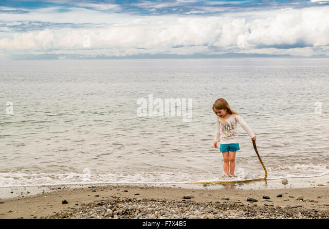 Girl standing on beach holding a stick - Stock Image
