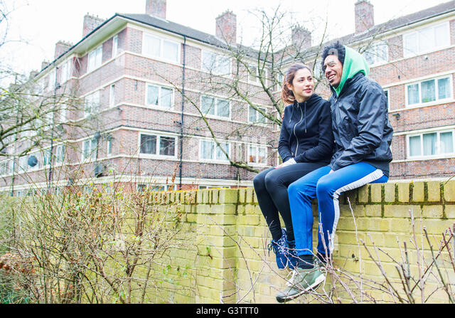 A young couple sitting on a wall together in Southwark Park in London. - Stock-Bilder