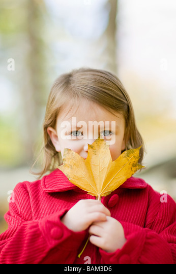Girl holding a leaf - Stock Image