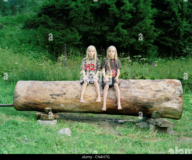Twin brothers on a log, Nowica, Poland - Stock Image