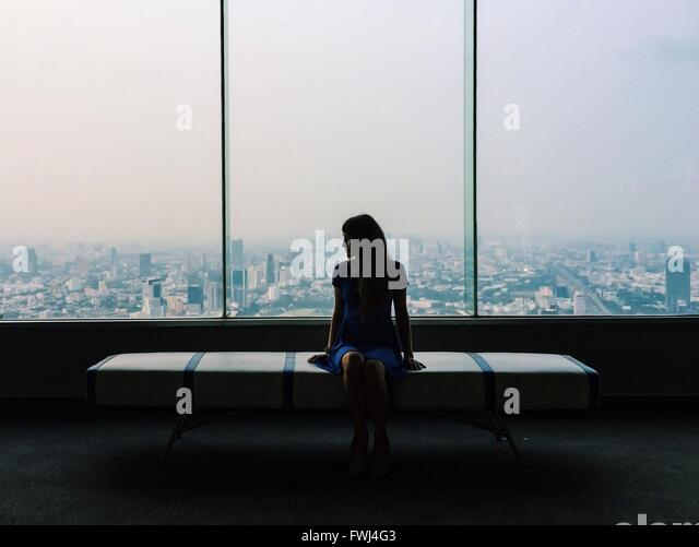 Young Woman In Blue Dress Sitting On Seat Against Glass Window In City - Stock Image