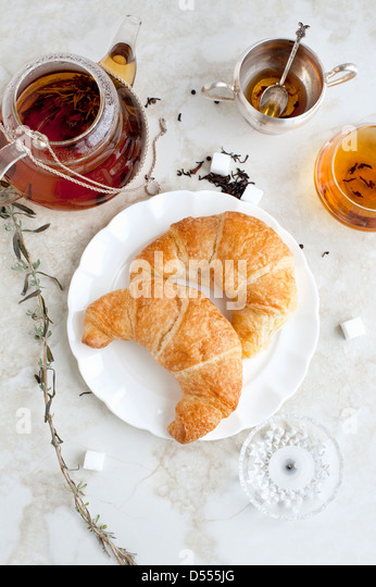 Croissants, honey and tea on table - Stock Image