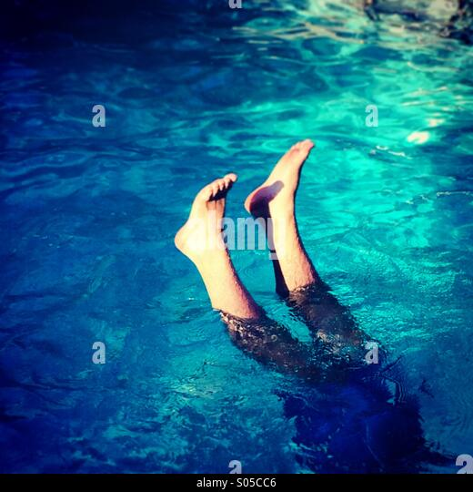 Feet sticking up from water - Stock Image
