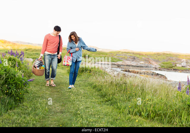 Full length front view of couple walking on field - Stock Image