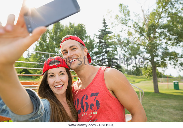 Couple taking cell phone pictures together in field - Stock Image