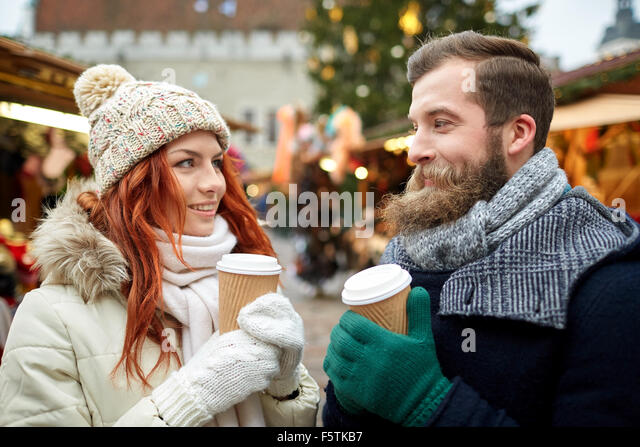 happy couple drinking coffee on old town street - Stock Image