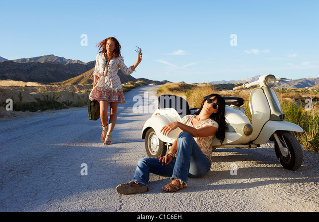Woman resting by road with motorbike - Stock Image