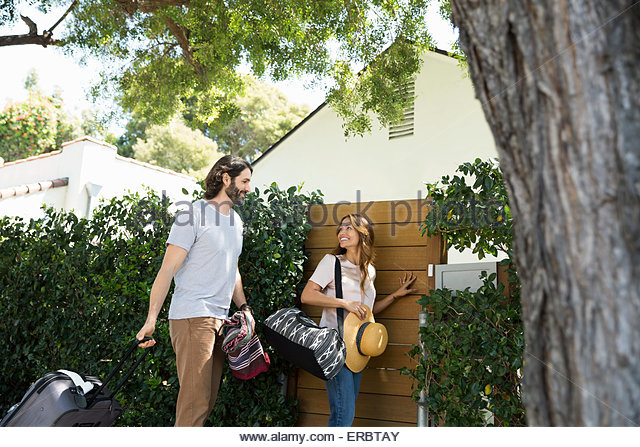 Couple with luggage arriving at vacation house gate - Stock-Bilder