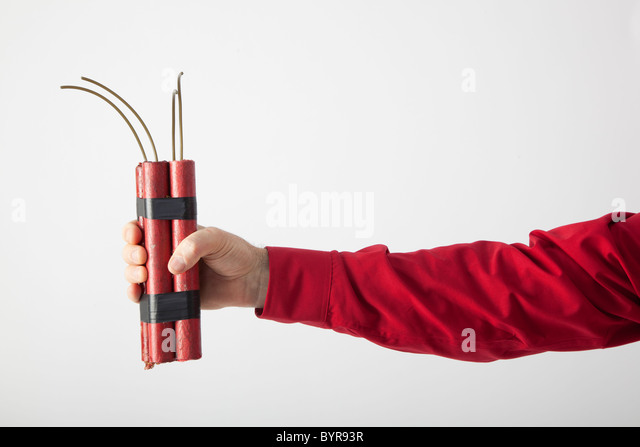 Man's arm holds TNT or dynamite explosive ready to light - Stock Image