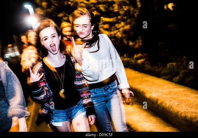 A group of 14 15 year old teenage girls friends with attitude together laughing having fun outside at night UK - Stock-Bilder