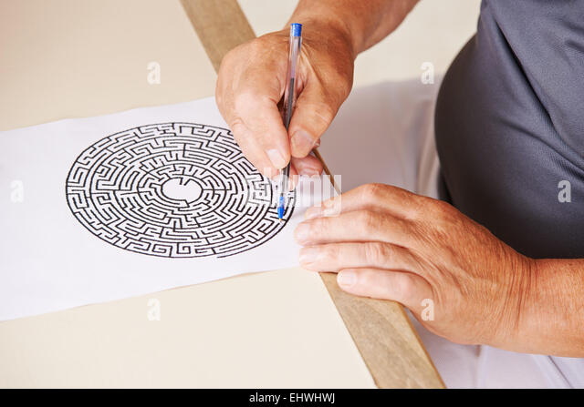 Old man doing memory training with paper maze in a nursing home - Stock-Bilder
