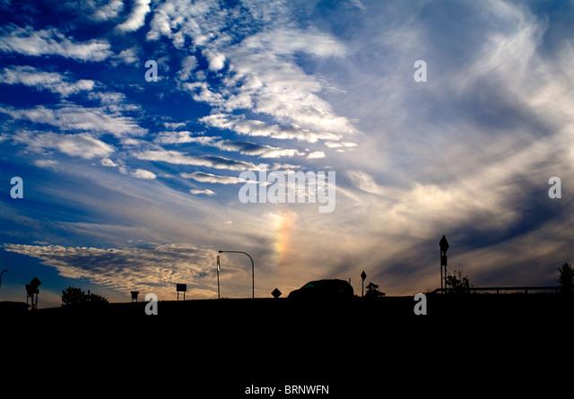 Rainbow cloud with minivan silhouette under blue sky. - Stock Image