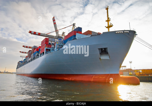 Cargo freight ship with stacked container at harbour terminal - Stock Image