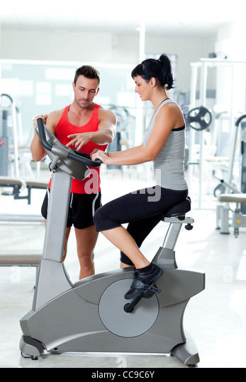 woman on stationary bicycle with personal trainer at fitness gym - Stock Image