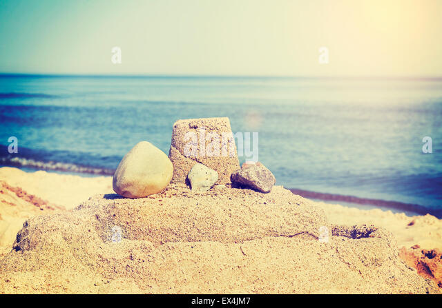 Vintage retro toned simple sandcastle on a beach, summer holidays concept. - Stock-Bilder
