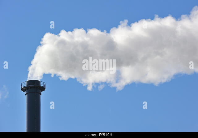 Conceptual image showing air pollution from industry showing chimney issuing fume into the atmosphere - Stock Image