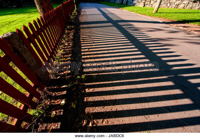 Dramatic photo of long shadows from fence in summer. - Stock Image