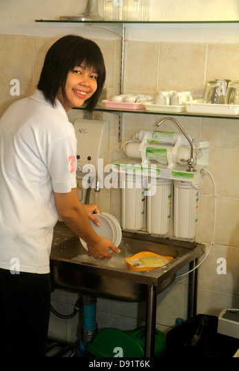 Bangkok Thailand Pathum Wan Soi Kasemsan 1 Rama 1 Road Asian woman job kitchen cleaning dishes restaurant smiling - Stock Image