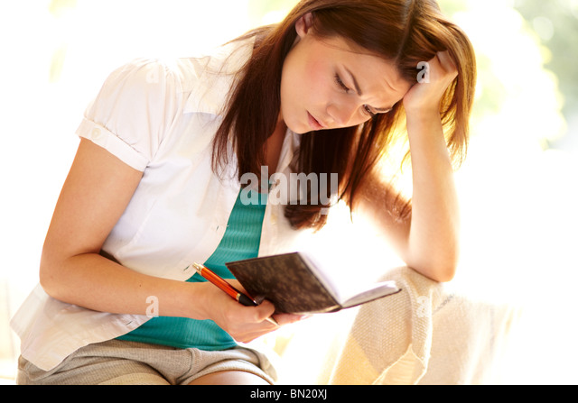 Girl looking in diary - Stock Image