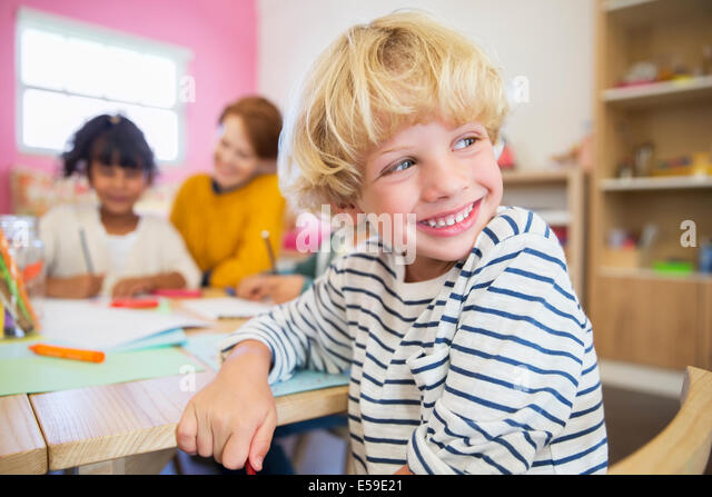 Student smiling in classroom - Stock Image