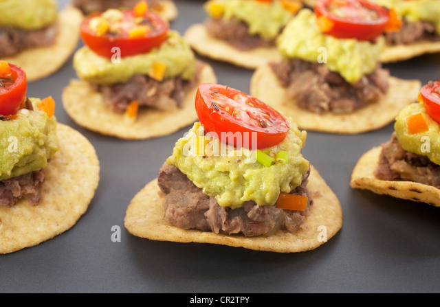 Spicy Mexican party food, corn chips topped with refried beans, avocado and tomato salsa. - Stock Image