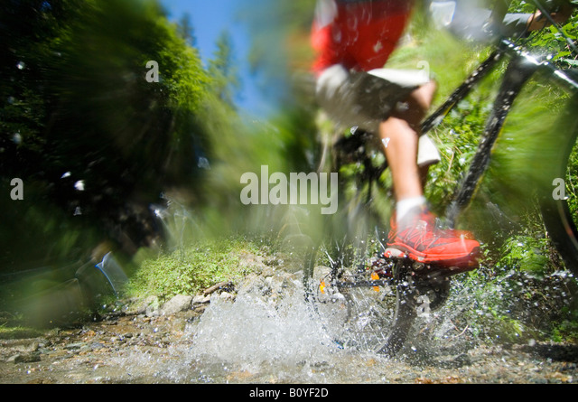 Mountainbiker crossing water, low section - Stock Image