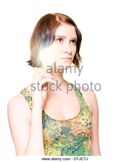 Perspective Portrait Of A Young Woman Holding Lit Up Yellow Light Bulb Looking Out To The Bright Future With Creative - Stock Image
