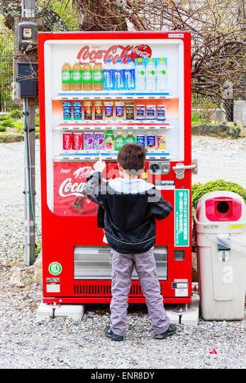 Japan. Caucasian boy, seen from behind, dwarfed by red Coca-Cola vending machine. Child choosing drink, pressing - Stock Image