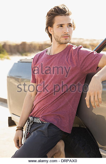 Man leaning against vehicle - Stock Image