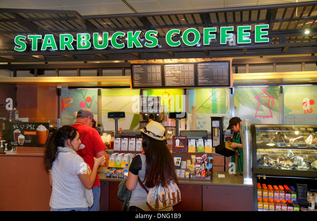 Texas Houston George Bush Intercontinental Airport IAH terminal concourse gate area Starbucks Coffee cafe counter - Stock Image