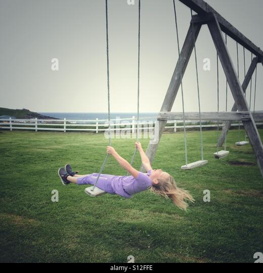 A girl on a swing at the seaside. - Stock Image