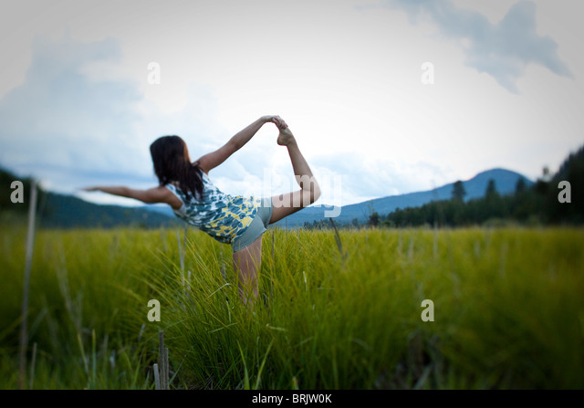 Young woman practices yoga in a grassy field. - Stock Image