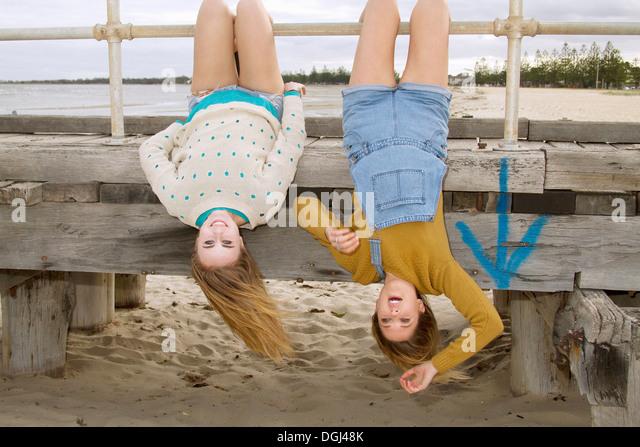 Girlfriends hanging upside down from pier - Stock-Bilder