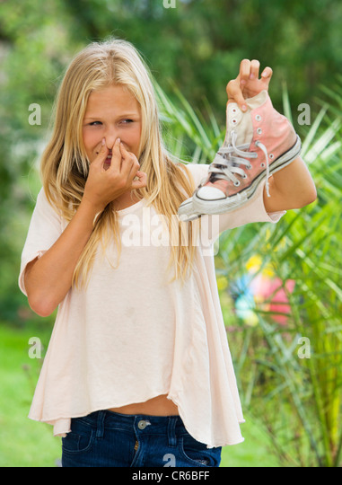 Austria, Teenage girl holding sneakers - Stock Image
