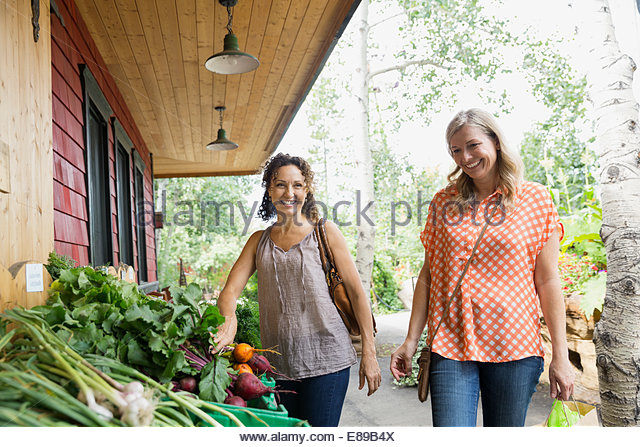 Smiling women shopping for produce outside market - Stock-Bilder