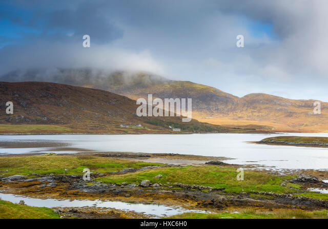 Tranquil scene clouds over rolling hills and lake, Loch Aineort, South Uist, Outer Hebrides - Stock Image
