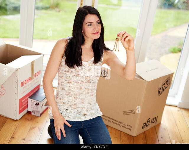 First time buyer holding keys to new house - Stock Image