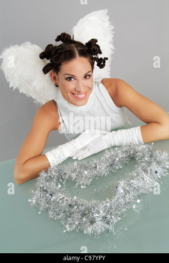 Funny Christmas angel with a silver dress and lametta - Stock Image